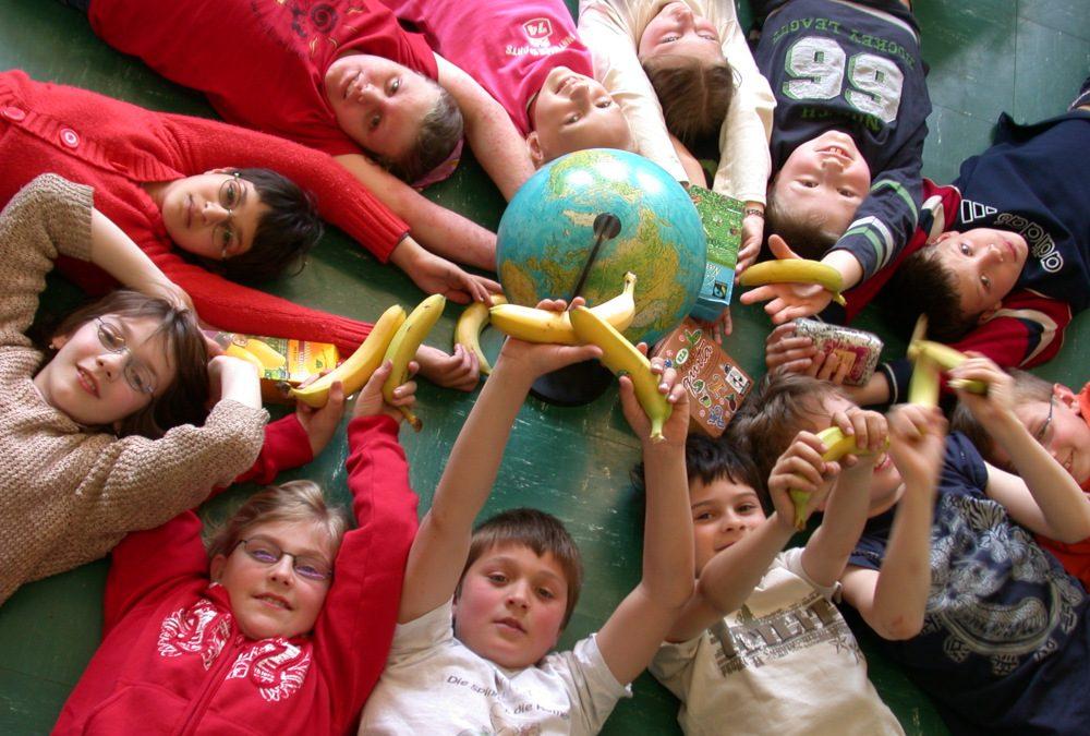 Kinder mit Erdball und Fair Trade Produkten